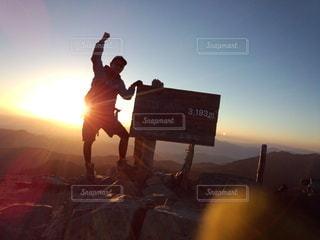 背景に夕日のある人の写真・画像素材[3206237]