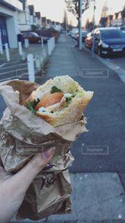 テーブルの上に座って半分食べたサンドイッチの写真・画像素材[3210035]