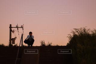 背景に夕日のある人の写真・画像素材[3211968]