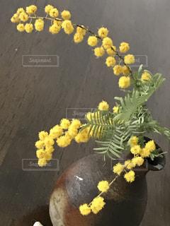 テーブルの上に花瓶に黄色い花の写真・画像素材[1159246]