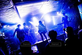 ステージの前の暗い部屋にいる人々のグループの写真・画像素材[3226421]