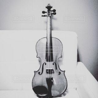ソファの上のヴァイオリンの写真・画像素材[3239466]