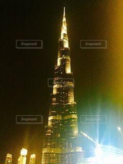 ブルジュ・ハリファを背景に夜にライトアップされた時計塔の写真・画像素材[3249873]