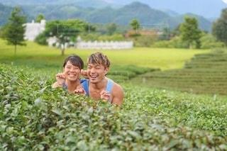 茶畑の景色に囲まれる笑顔の2人の写真・画像素材[2393139]
