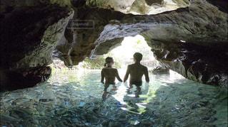 洞窟の中から撮った男女のシルエットの写真・画像素材[2431669]
