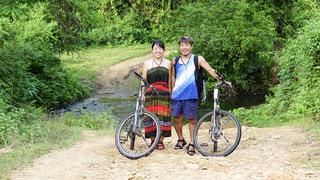 でこぼこの泥道を自転車で旅する2人の写真・画像素材[2431670]
