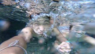 川の中を手を繋いで泳いでいるカップルの写真・画像素材[2431675]