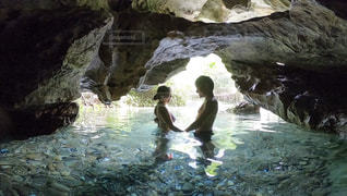 洞窟の中から撮った男女のシルエットの写真・画像素材[2431676]