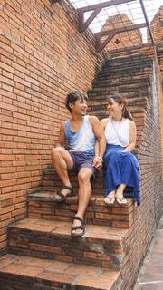 レンガの建物の階段で座る二人の写真・画像素材[2473345]