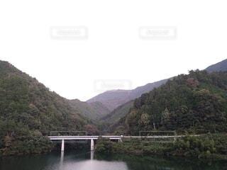 山を背景にした水の体に架かる橋の写真・画像素材[3777174]