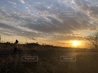 草原に沈む夕日と子供の写真・画像素材[3306422]