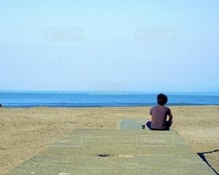ビーチに座っている男の写真・画像素材[3638073]