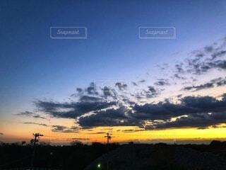 電柱のシルエットと日没時の空の雲のクローズアップの写真・画像素材[3796842]