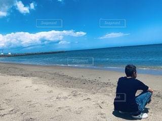 砂浜の上に座っている男の写真・画像素材[3352926]