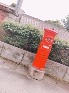 建物の側面に座っている赤い消火栓の写真・画像素材[3292107]