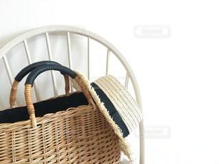 白い椅子の上のかごバッグと帽子の写真・画像素材[3343563]