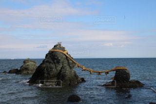 水の体の真ん中に岩の上に座っている男の写真・画像素材[972475]