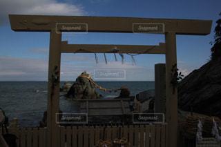 水の体の横に木製のベンチの写真・画像素材[972486]