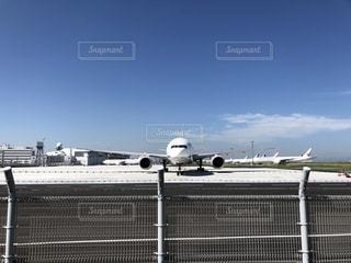 フェンスの側面に停まっている飛行機の写真・画像素材[3380735]