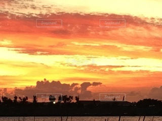 背景に都市がある水域に沈む夕日の写真・画像素材[3304545]