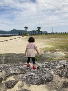 水の体の隣に立っている少年の写真・画像素材[3333154]
