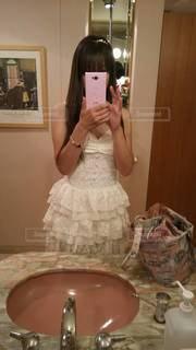鏡の前に立ってカメラのポーズをとる女性の写真・画像素材[3310886]
