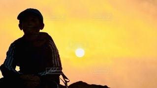 背景に夕日のある人の写真・画像素材[3313934]