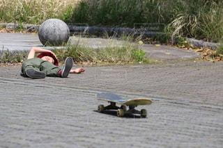 地面に横たわるスケートボードに乗っている人の写真・画像素材[3313940]