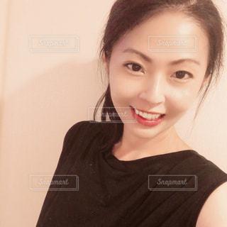 黒いシャツを着てカメラに向かって微笑む女性の写真・画像素材[3332245]