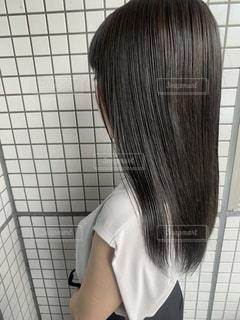 タイル張りの壁の前に立っている人の写真・画像素材[3345435]