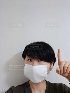 マスクをつけて上を指している人の写真・画像素材[3402150]