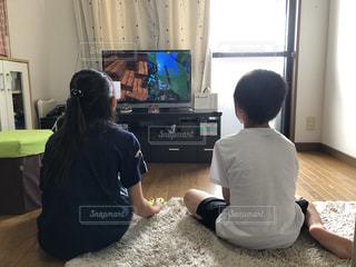 テレビの前に座ってビデオゲームをしている子供たちの写真・画像素材[3364906]