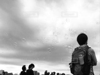 曇った空とシャボン玉の写真・画像素材[3700872]