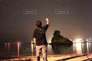 夜空に向かって手を掲げる男2の写真・画像素材[4771632]