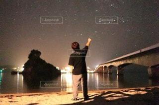 夜空に向かって手を掲げる男の写真・画像素材[4771633]