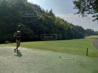 青空のもと 木々に囲まれたゴルフコースでゴルフを楽しむ男性の写真・画像素材[3641224]