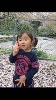 塀の隣に立っている小さな男の子の写真・画像素材[3388126]