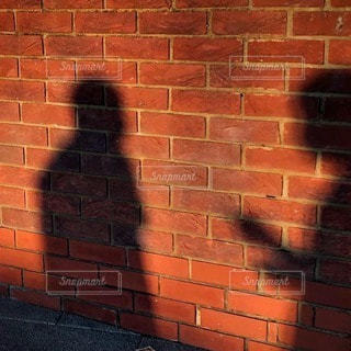レンガの壁の絵で話し合う人影の写真・画像素材[3390765]