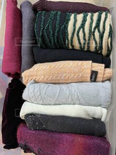 畳んでケースに仕舞われたセーター類の写真・画像素材[4294782]