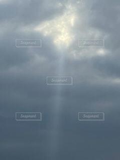 暗い雲の合間から光の柱が降りているの写真・画像素材[4339818]