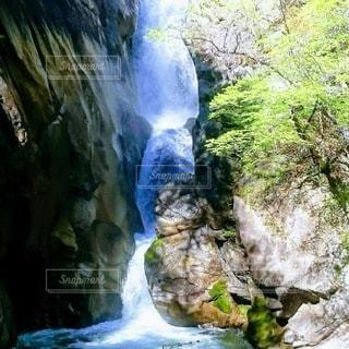 鋭く切り立った岩肌の間を流れ落ちる滝の写真・画像素材[3413466]