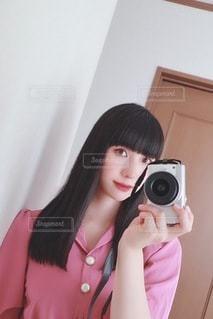 鏡の前に立ってカメラのポーズをとる人の写真・画像素材[3574279]