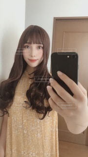 鏡の前に立ってカメラのポーズをとる女性の写真・画像素材[3628784]