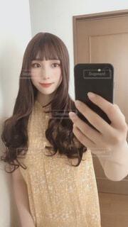 鏡の前に立ってカメラのポーズをとる女性の写真・画像素材[3628783]