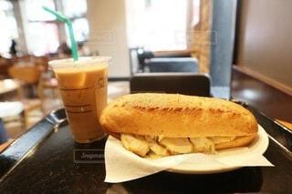 テーブルの上に乗っているサンドイッチとカフェオレの写真・画像素材[3701767]