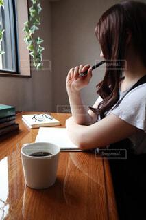 コーヒーを飲みながらペンを持つ女性の写真・画像素材[4570399]