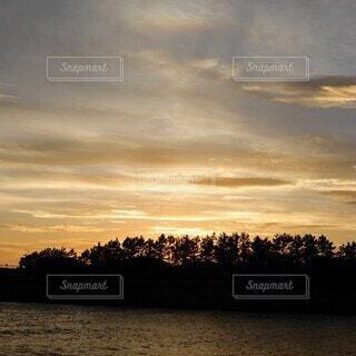 東京湾の河口の林に沈む夕日とオレンジ色の夕焼け空の写真・画像素材[3662894]
