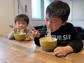 麺をすする兄弟の写真・画像素材[4372442]