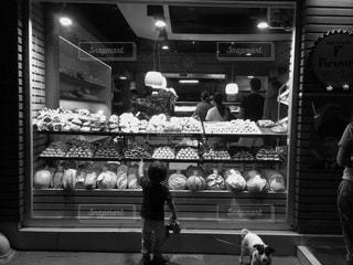 店の窓の前に立っている人の写真・画像素材[3462443]