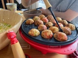 食べ物の皿を持ったテーブルに座っている人の写真・画像素材[3471464]